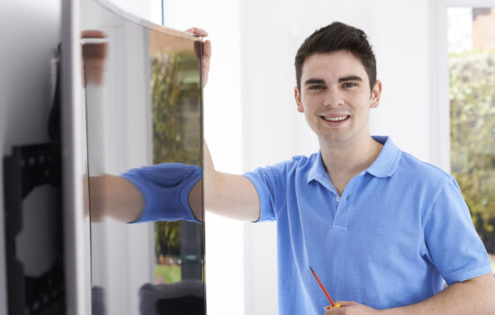 57482725 - engineer fitting curved screen television in home